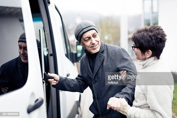 nurse helping senior man enter a van