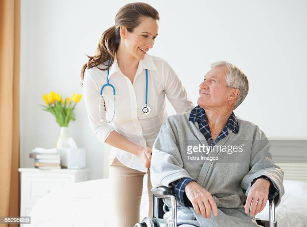 nurse helping senior man in wheelchair - hospice stock pictures, royalty-free photos & images