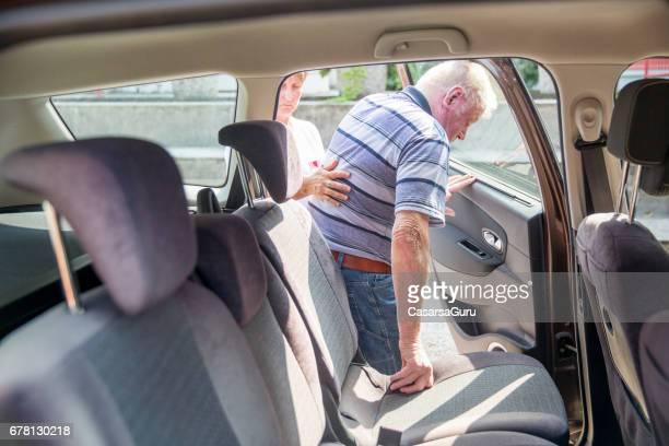 Nurse Helping Senior Man to get in the Car