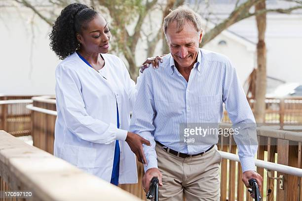 nurse helping senior man with walker - african american man helping elderly stock pictures, royalty-free photos & images