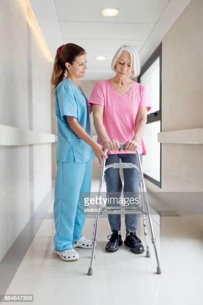 Infirmière aide senior patient dans l'utilisation de walker de mobilité