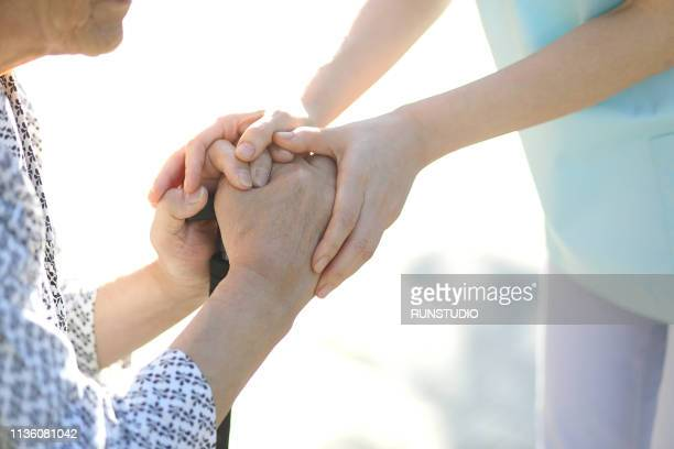 nurse helping senior patient with cane - nursing assistant stock pictures, royalty-free photos & images