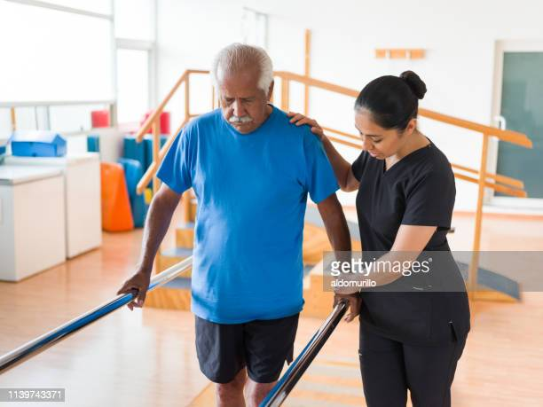 nurse helping senior student walk in parallel bars - recovery stock pictures, royalty-free photos & images