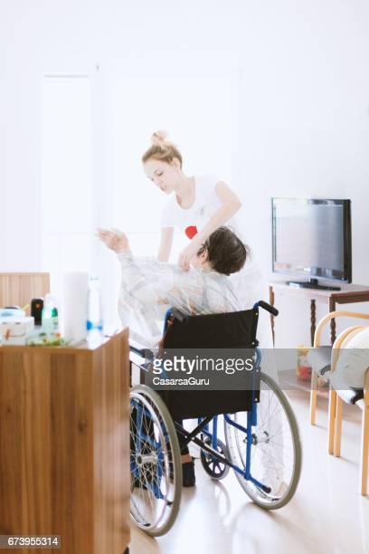 nurse helping senior woman dressing - residential care stock photos and pictures