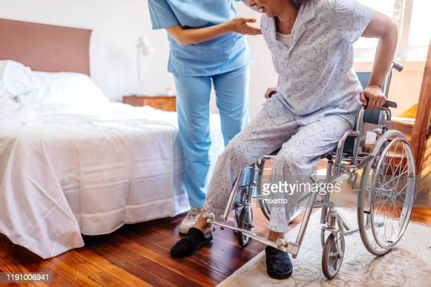 infirmière aidant la femme aînée se lever du fauteuil roulant - chambre hopital photos et images de collection