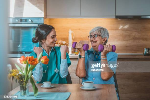 nurse helping senior woman in lifting dumbbells - physical therapy stock pictures, royalty-free photos & images