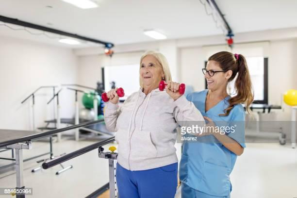 Nurse helping senior woman in lifting dumbbells