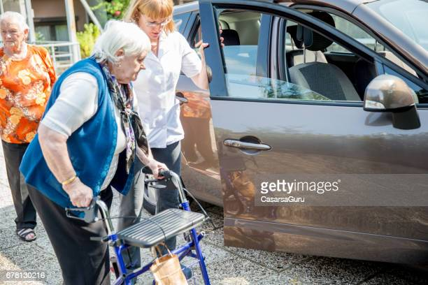 Nurse Helping Senior Woman to get in the Car