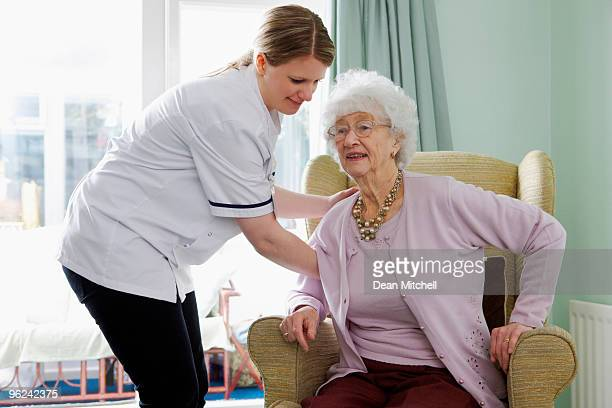 Nurse helping senior woman to her feet in care home
