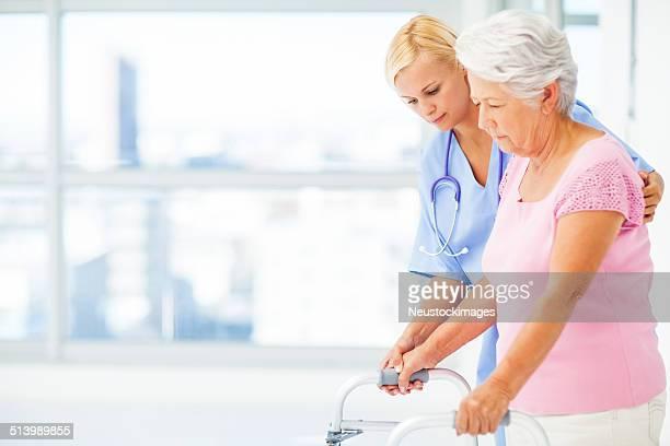 Krankenschwester helfen Senior Frau mit Walker