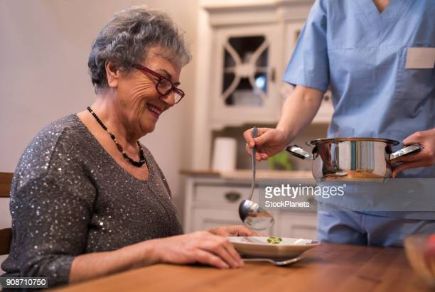 nurse helping senior women at home - home carer stock photos and pictures