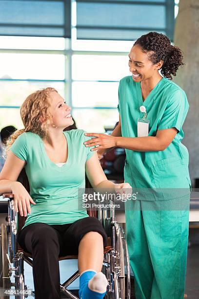 Jeune infirmière aide un patient à l'Hôpital de rééducation avec physiothérapie