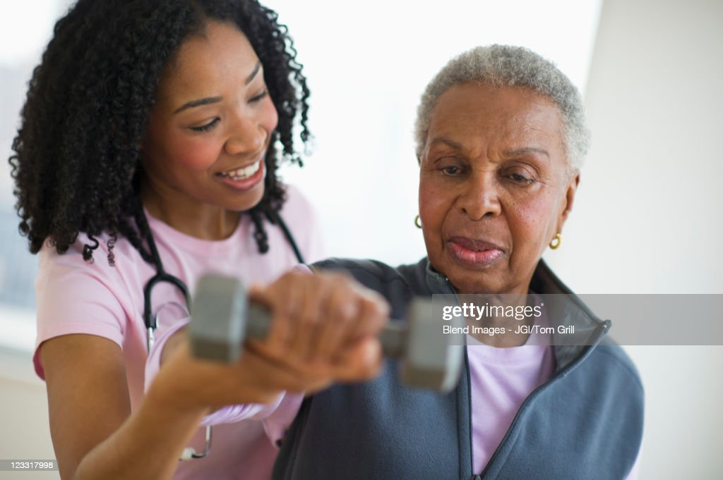 Nurse helping woman exercise with dumbbell : Stock Photo
