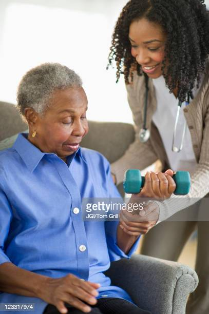 Nurse helping woman exercise with dumbbells