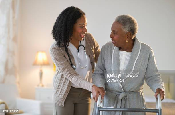 Nurse helping woman walk with walker