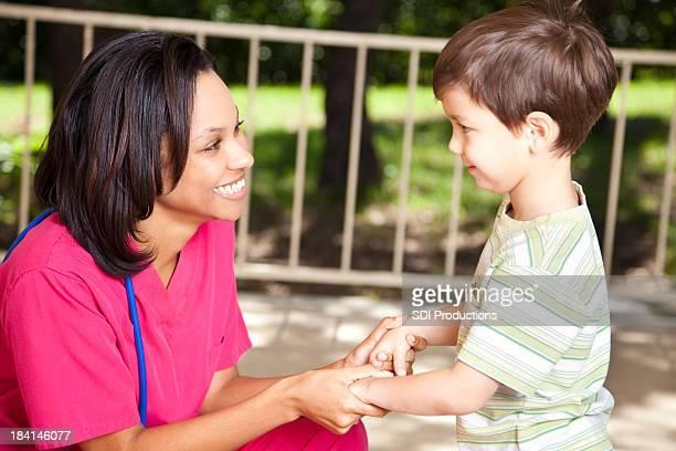 Infermiera aiutando la giovane ragazzo all'aperto