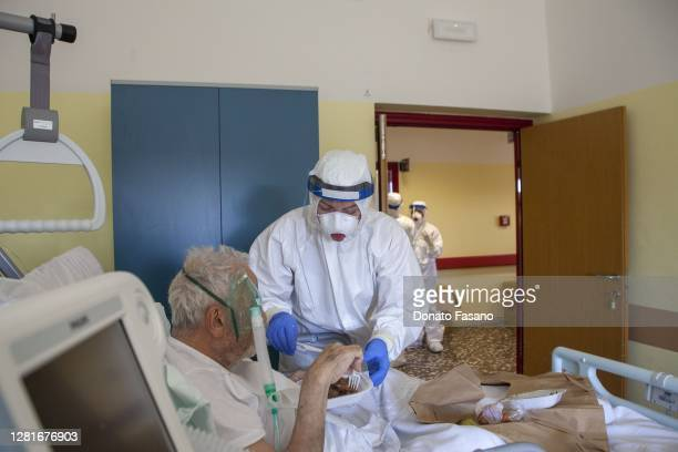 A nurse helps a patient with a meal at Bari Hospital on October 22 2020 in Bari Italy New infections from Covid in Puglia have sprung up in the last...
