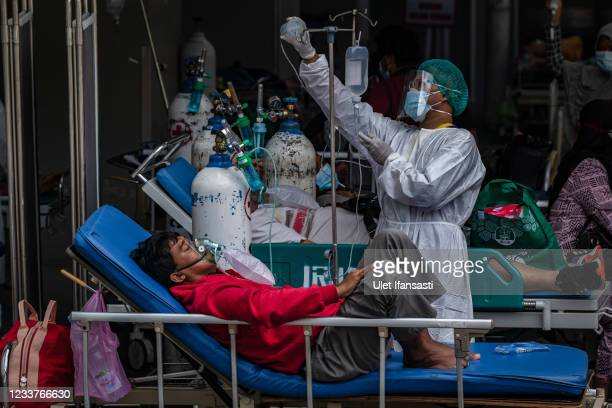 Nurse helps a patient with her IV at outside an emergency room due to an overflow of Covid-19 patients at a hospital on July 2, 2021 in Semarang,...