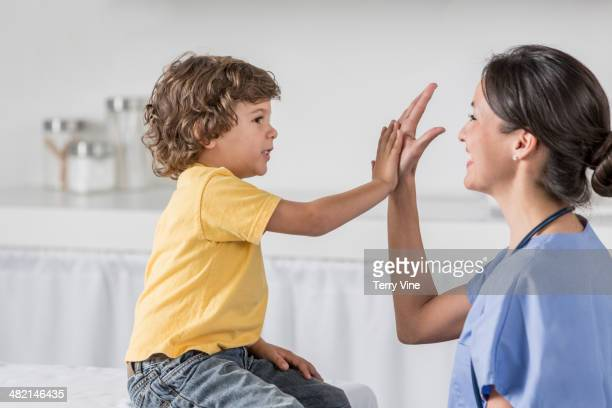 Nurse high fiving boy in doctor's office