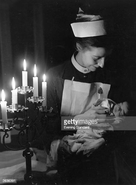 A nurse holding a baby by candle light in the maternity unit at St Andrew's Hospital Dollis Hill during the energy dispute