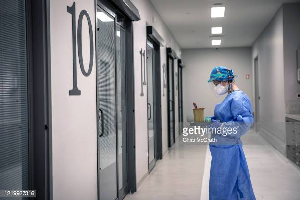 A nurse holding a COVID19 test waits to enter an emergency room to perform the test on a patient in the dedicated COVID19 emergency ward at the...