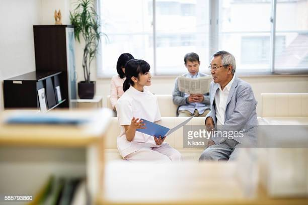 Nurse holding document and talking to senior patient
