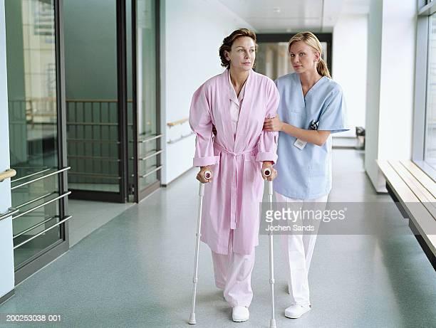 Infirmière tenant female patient à béquilles à l'hôpital corridor