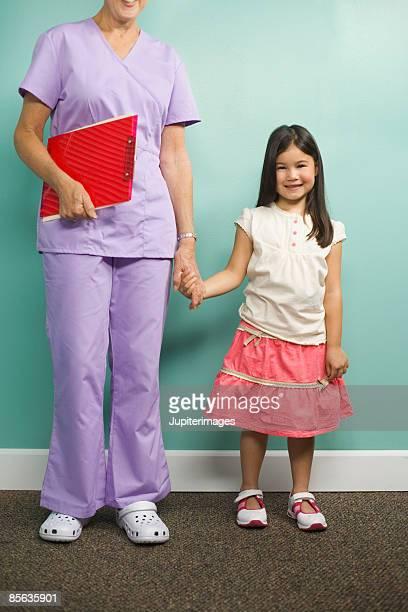 nurse holding girls hand - indonesia map stockfoto's en -beelden