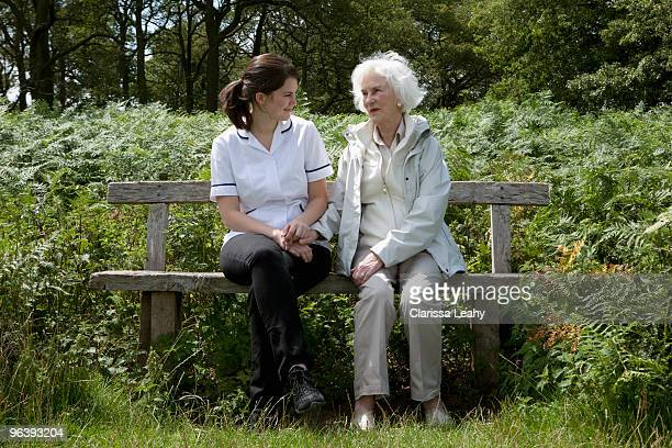 Nurse holding hand of elderly woman