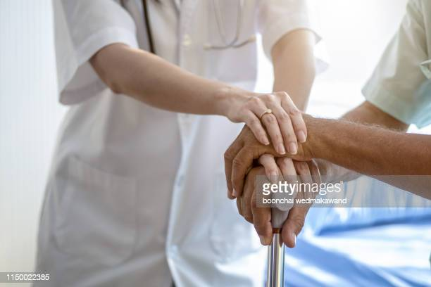 nurse holding hand of senior man in rest home - hospice stock pictures, royalty-free photos & images