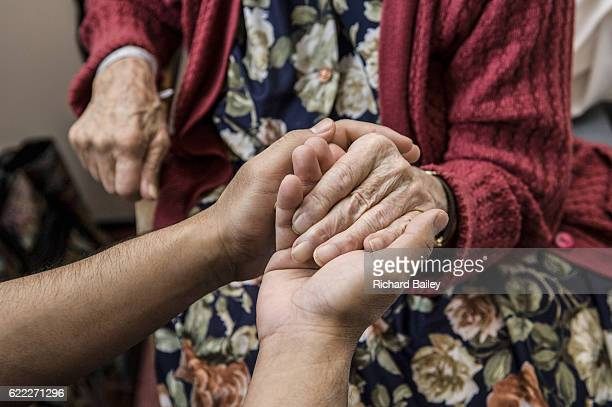 nurse holding hands with elderly patient. - care home stock pictures, royalty-free photos & images