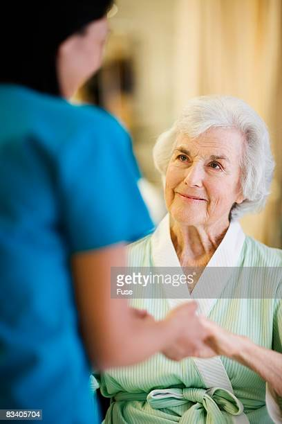 nurse holding hands with elderly patient - gerontology stock pictures, royalty-free photos & images