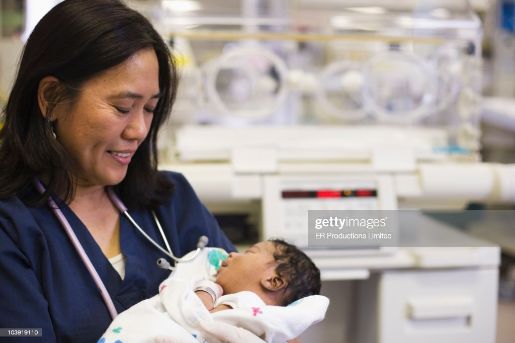 Nurse holding newborn baby in hospital nursery : Stock Photo