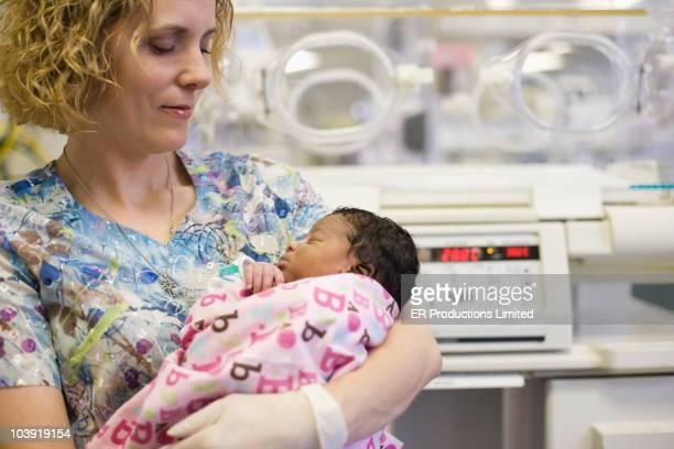 Nurse holding newborn baby in hospital nursery