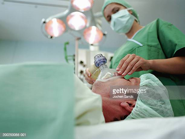 Nurse holding oxygen mask to male patient's face in operating theatre