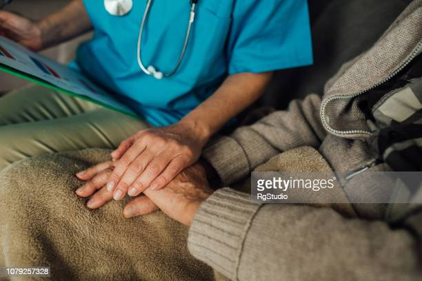 nurse holding patient's hand - house call stock pictures, royalty-free photos & images