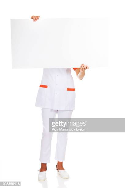 nurse holding placard standing against white background - nursing slogans stock photos and pictures