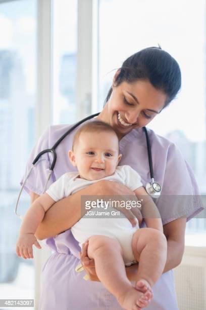 Nurse holding smiling baby