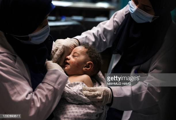 Nurse holds a Omar al-Hadidi, who was pulled alive from under the rubble while seven other family members perished, at Al-Shifa Hospital, after an...