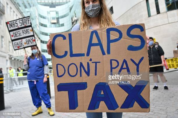 A nurse holds a placard as they demonstrate in London on September 12 2020 calling for a pay rise for NHS nursing staff