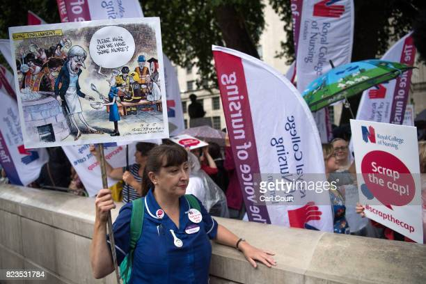 A nurse holds a placard during a protest outside Downing Street on July 27 2017 in London England The Royal College of Nursing have launched a series...