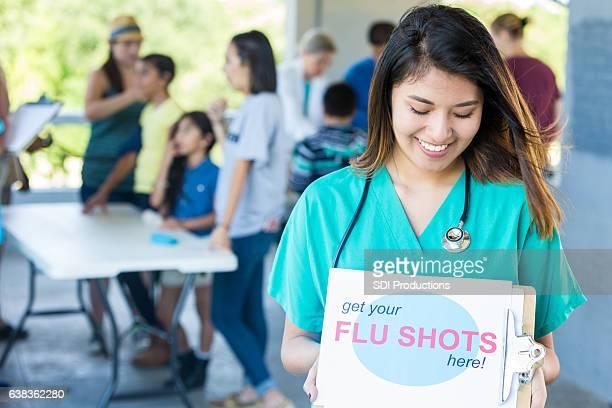 Nurse holds a sign promoting flu shots at health fair