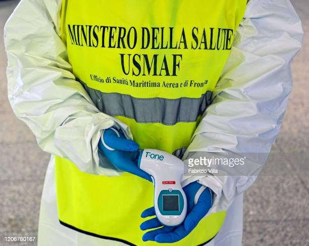 A nurse holds a thermometer being used to measure the body temperature of passengers arriving at Catania airport on March 12 2020 in Catania Italy...