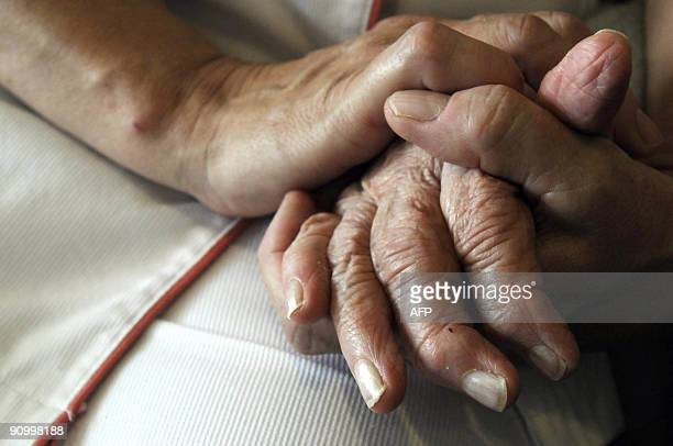 A nurse holds the hands of a person suffering from Alzheimer's disease on September 21 2009 at Les Fontaines retirement home in Lutterbach eastern...