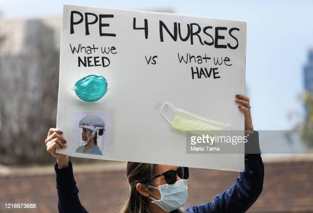 A nurse holds up a sign to protest the lack of personal protective gear available at UCI Medical Center amid the coronavirus pandemic on April 3 2020...