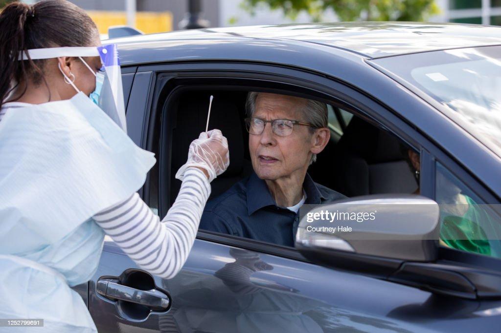看護師は、彼女がドライブスルーテストセンターで彼のCovid-19テストを行う方法を患者に示すために綿棒を保持します : ストックフォト