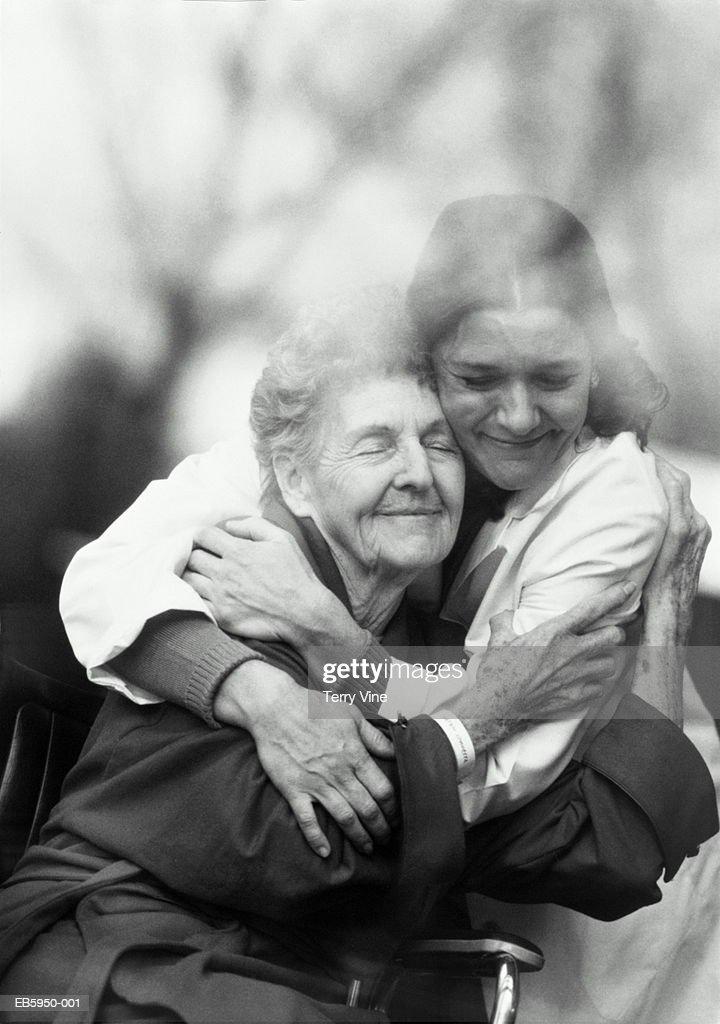 Nurse hugging elderly patient in wheelchair (B&W) : Bildbanksbilder