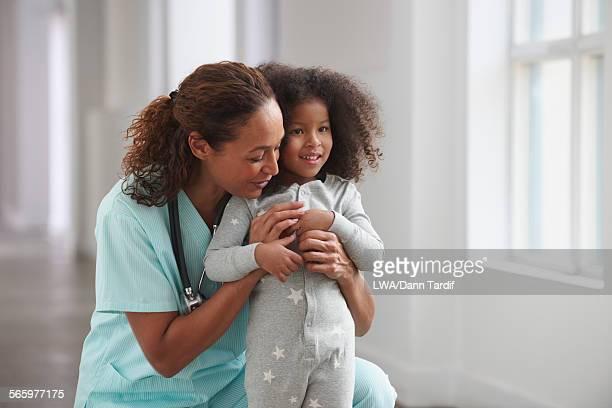 Nurse hugging girl in hallway