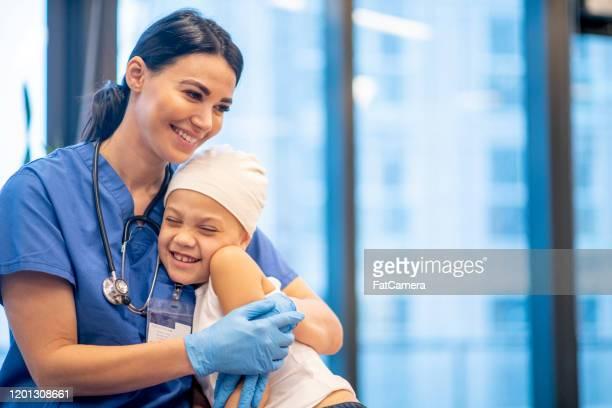 若いがん患者の写真を抱きしめる看護師 - cancer illness ストックフォトと画像