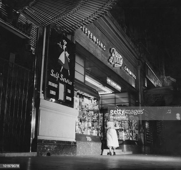 A nurse hurries from a latenight opening branch of Boots the Chemists with urgently needed drugs Piccadilly Circus London 1955 The shop is next to...